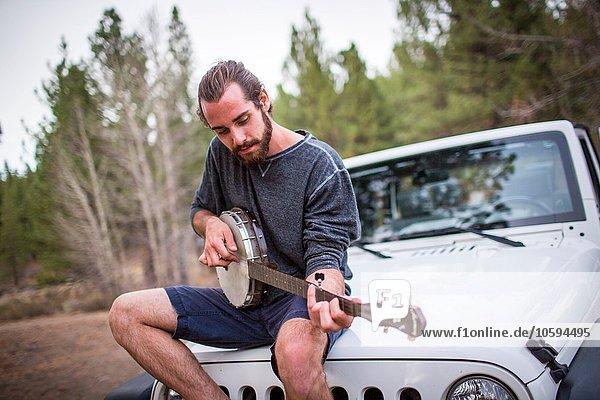 Junger Mann spielt Banjo auf Jeep-Haube  Lake Tahoe  Nevada  USA