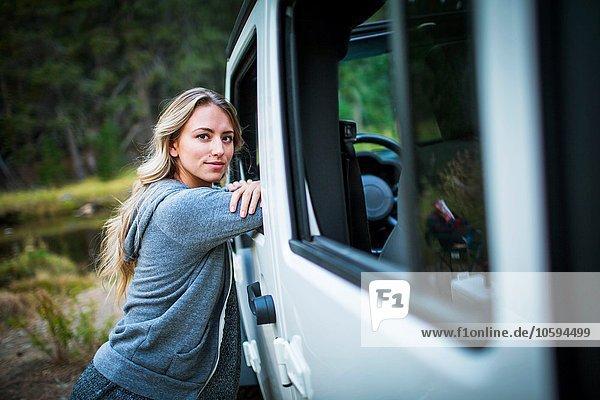 Porträt einer jungen Frau  die sich am Flussufer  Lake Tahoe  Nevada  USA  gegen den Jeep lehnt.
