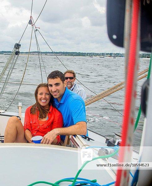 Ein Paar entspannt sich auf einem Segelboot und schaut lächelnd in die Kamera.