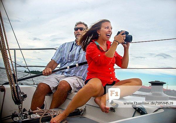 Junge Frau sitzt auf einem Segelboot und fotografiert lächelnd