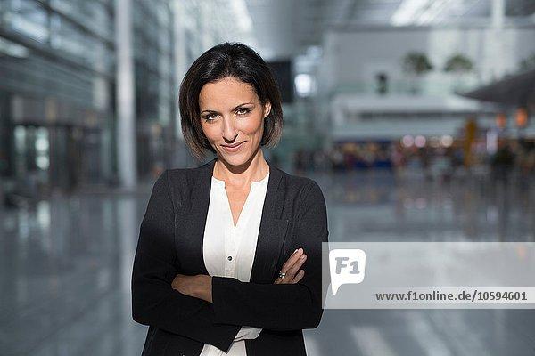 Portrait einer reifen Geschäftsfrau mit gefalteten Armen am Flughafen