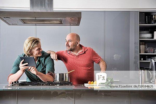 Männliches Paar  das beim Zubereiten von Speisen in der Küche auf digitale Tabletten schaut