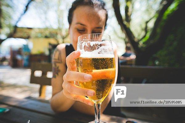 Frau hält ein Glas Bier hoch  Garda  Italien