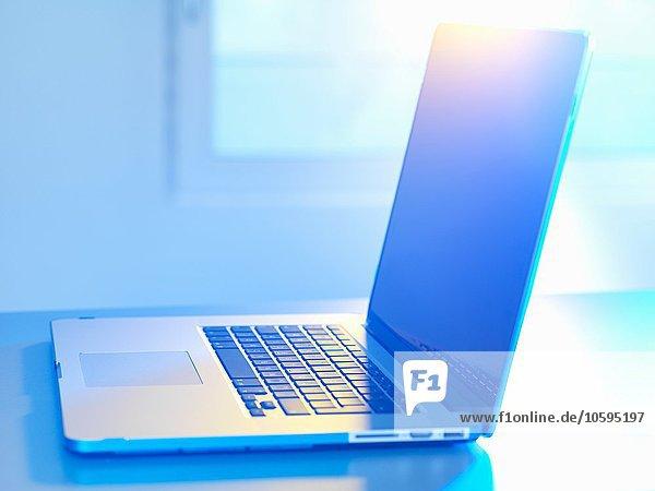 Seitenansicht des offenen Laptops auf dem Schreibtisch  Sonnenlicht kommt durch das Fenster