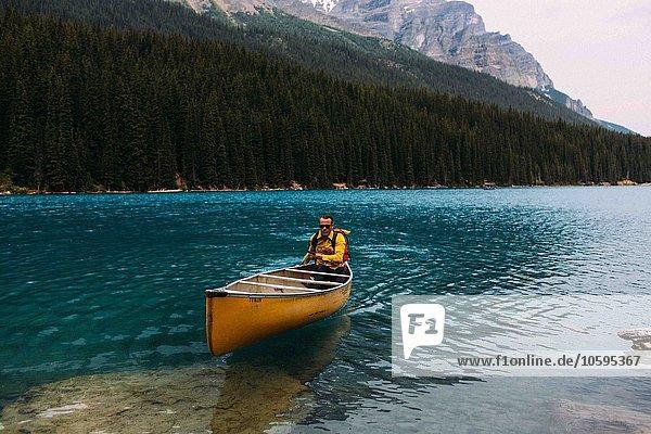 Mid adult man paddeln Kanu auf Moraine Lake  Blick auf die Kamera  Banff National Park  Alberta Kanada