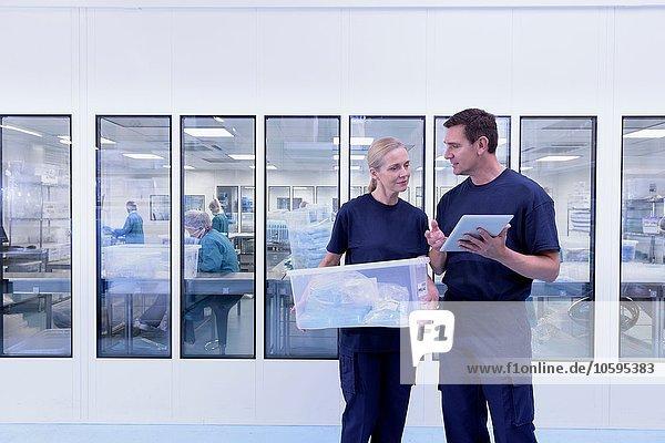 Mitarbeiter mit digitaler Tablettenkontrolle außerhalb des Reinraums in der Fabrik für chirurgische Instrumente