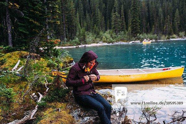 Mittlerer erwachsener Mann im Kanu auf dem Moraine Lake  Blick nach unten  wasserdichter Mantel  Banff National Park  Alberta Canada