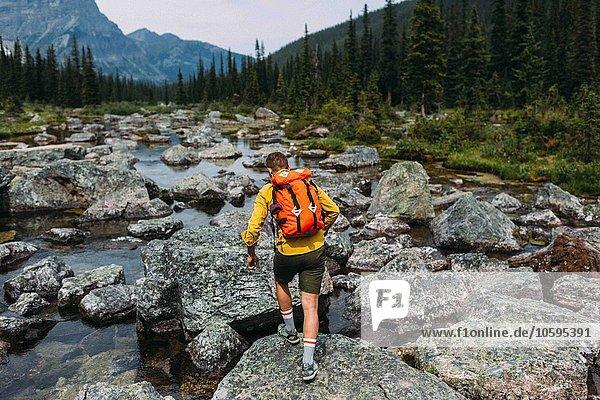 Rückansicht eines erwachsenen Mannes mit Rucksack auf felsigem Flussbett  Moraine Lake  Banff National Park  Alberta Canada