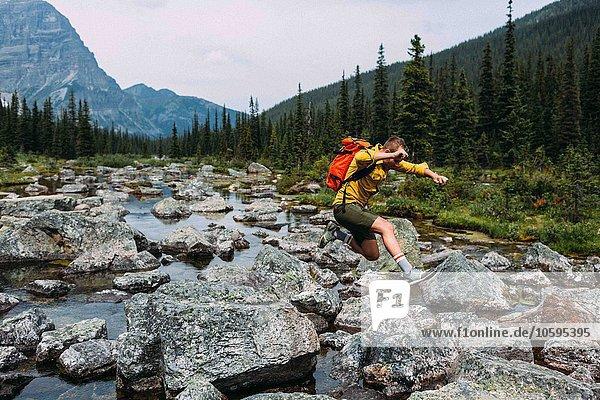 Seitenansicht eines erwachsenen Mannes mit Rucksack über felsigem Flussbett  Moraine Lake  Banff National Park  Alberta Canada