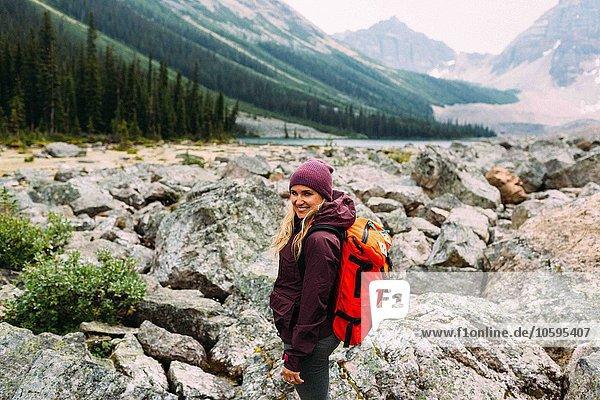 Seitenansicht einer erwachsenen Frau auf einer felsigen Landschaft mit Rucksack und Blick auf die lächelnde Kamera  Moraine Lake  Banff National Park  Alberta Canada