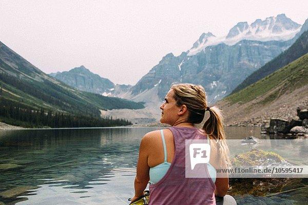 Rückansicht der mittleren erwachsenen Frau  die am Wasser sitzt und wegschaut  Moraine Lake  Banff National Park  Alberta Canada