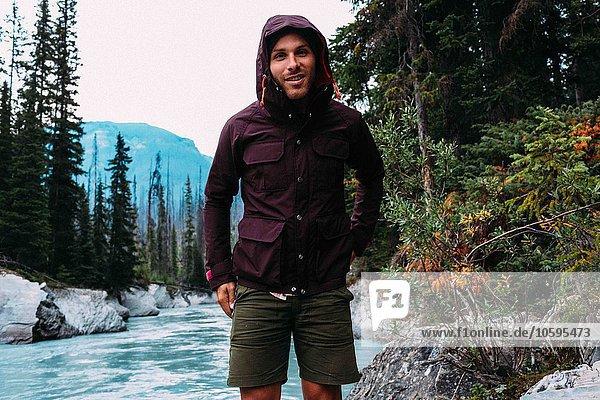Mittlerer Erwachsener Mann am Fluss mit wasserdichtem Kapuzenmantel  der lächelnd auf die Kamera schaut  Moraine Lake  Banff National Park  Alberta Canada