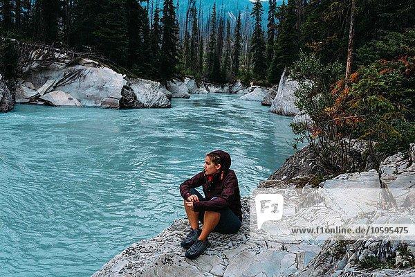 Hochwinkelansicht einer erwachsenen Frau am Wasser sitzend  Moraine Lake  Banff National Park  Alberta Canada