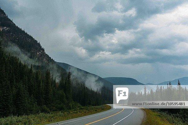 Verminderte Aussicht auf leere  offene Straßen und neblige Bergketten  Moränensee  Banff Nationalpark  Alberta Canada
