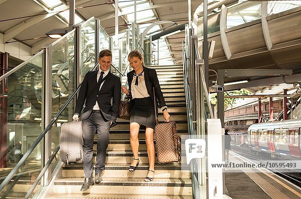 Businessman and businesswoman coming down stairs  Underground station  London  UK