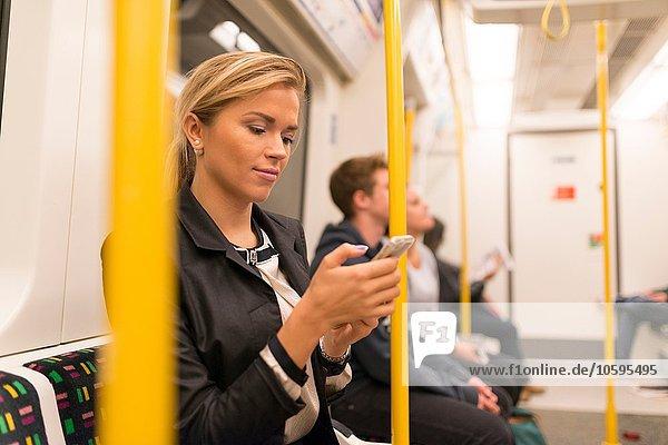 Geschäftsfrau texting on tube  London Underground  UK