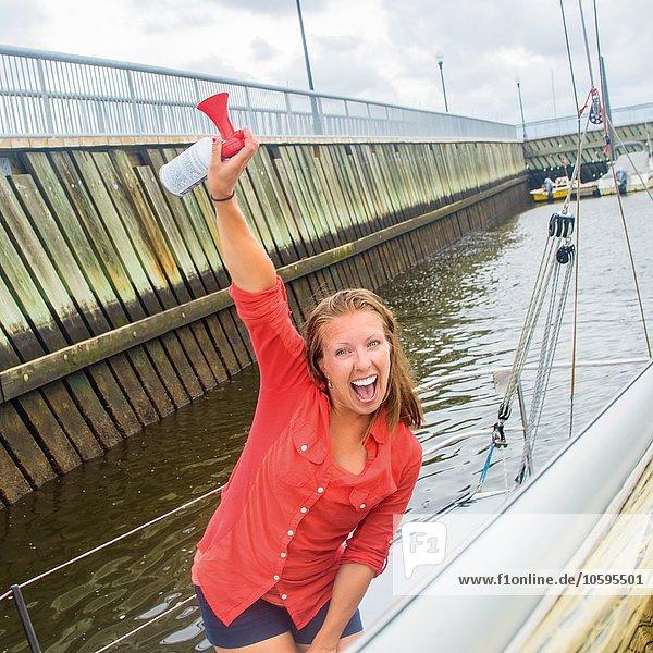 Junge Frau auf Segelboot im Yachthafen Arm erhoben haltend Luft Horn  Blick auf die Kamera offen Mund lächelnd