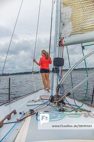 Durchgehende Rückansicht der jungen Frau auf dem Bug des Segelbootes mit Blick nach hinten