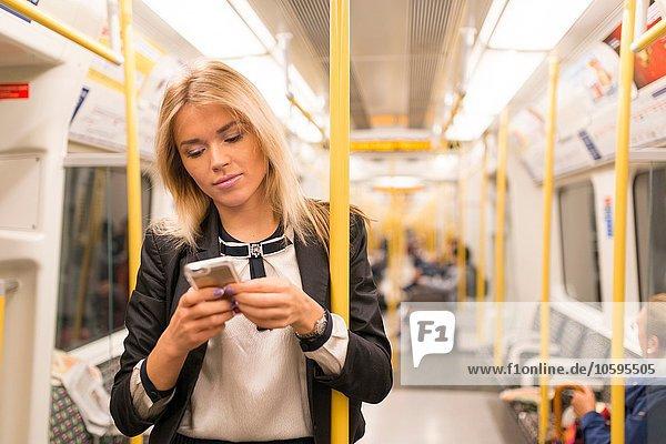 Geschäftsfrau texting on tube  London Underground  UK Geschäftsfrau texting on tube, London Underground, UK