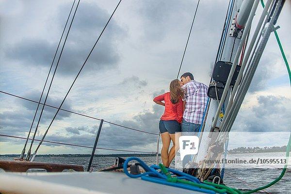 Rückansicht des Paares am Bug des Bootes beim Küssen