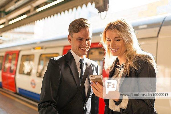 Businessman and businesswoman texting on platform  Underground station  London  UK