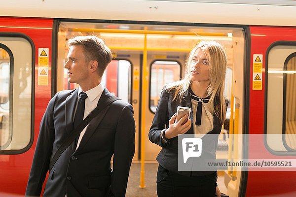 Businessman and businesswoman alighting train  London Underground  UK
