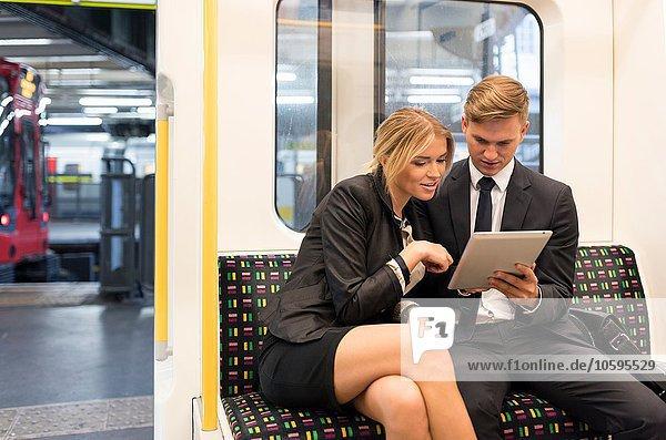 Geschäftsmann und Geschäftsfrau teilen sich ein digitales Tablett  London Underground  UK Geschäftsmann und Geschäftsfrau teilen sich ein digitales Tablett, London Underground, UK