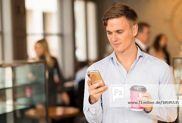 Mann mit Kaffee zum Mitnehmen per Smartphone Mann mit Kaffee zum Mitnehmen per Smartphone