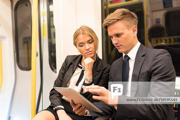 Businessman and businesswoman sharing digital tablet  London Underground  UK