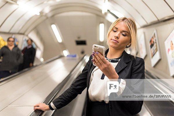 Businesswoman texting on escalator  London Underground  UK