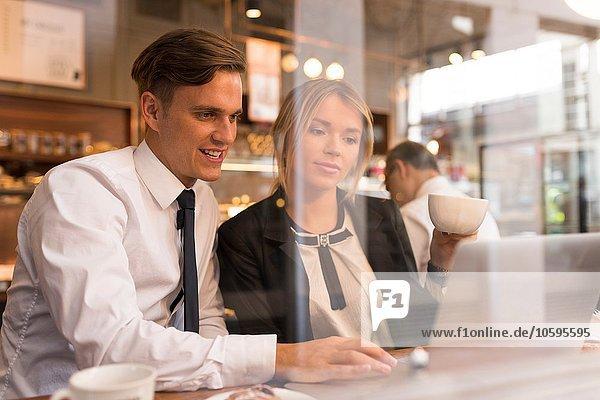 Geschäftsmann und Geschäftsfrau bei der Arbeit am Laptop im Cafe