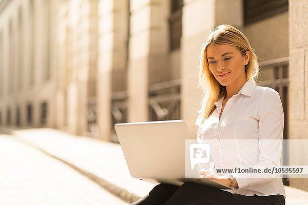 Businesswoman using laptop on kerb  London  UK