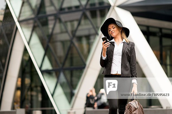 Woman texting while walking  30 St Mary Axe in background  London  UK