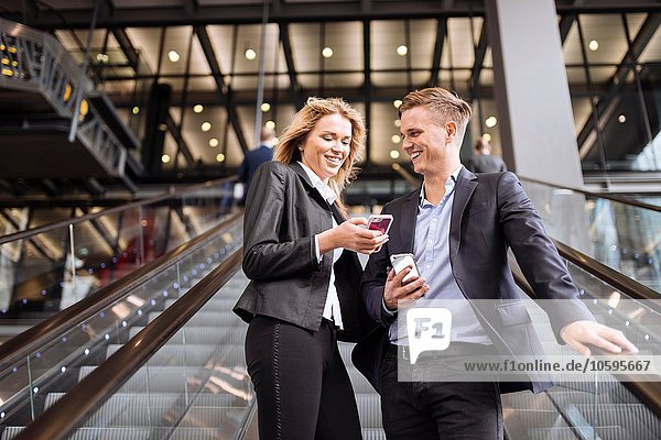 Geschäftsmann und Geschäftsfrau auf Rolltreppe  London  UK