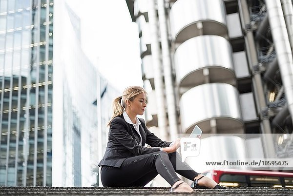 Businesswoman using digital tablet in street  London  UK