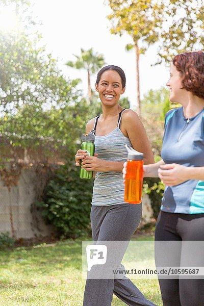 Junge Frauen in Sportbekleidung mit Wasserflaschen lachend unterwegs