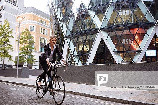 Businesswoman on bike passing 30 St Mary Axe  London  UK