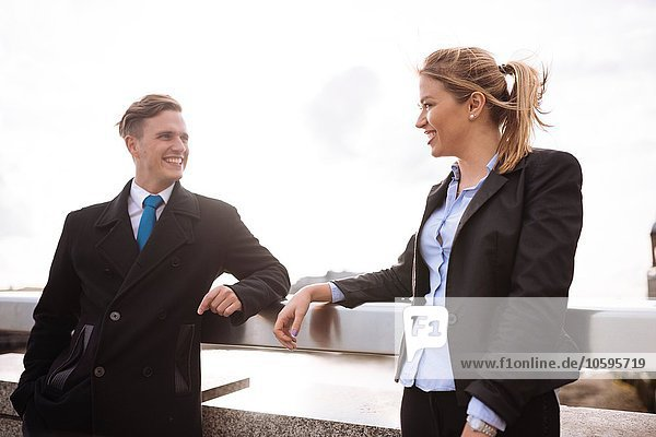 Businessman and businesswoman leaning on rail