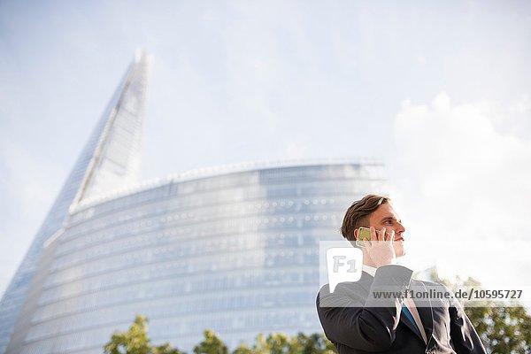 Geschäftsmann beim Telefonieren  Gebäude im Hintergrund  London  UK Geschäftsmann beim Telefonieren, Gebäude im Hintergrund, London, UK