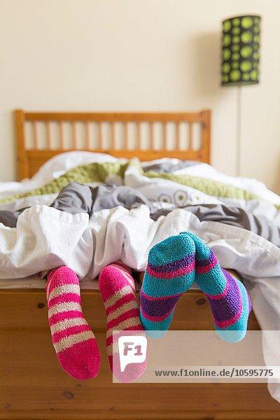 Junge Frauen im Bett unter der Bettdecke  Sockenfüße aus dem Bett herausragend