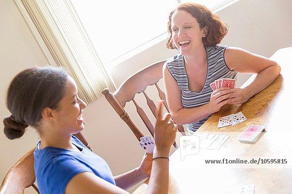 Hoher Blickwinkel auf junge Frauen  die am Esstisch sitzen und lächelnd Karten spielen.