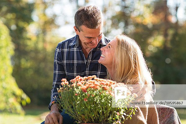 Altes Paar im Garten mit Topfpflanze