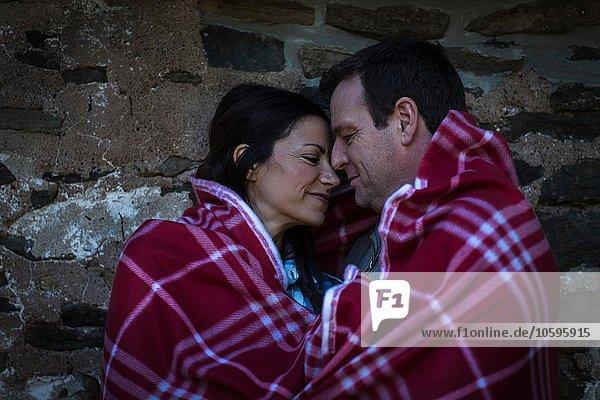 Romantisches reifes Paar von Angesicht zu Angesicht in Decke gehüllt in der Nacht
