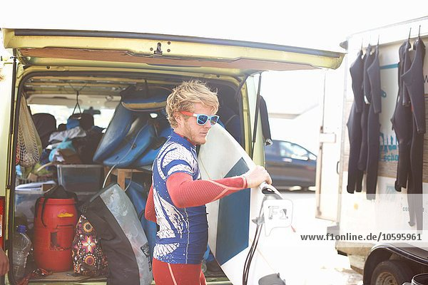 Male surfer standing by open van  holding surfboard