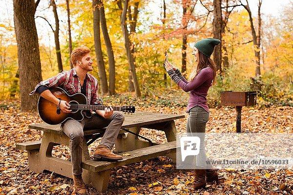 Junge Frau fotografiert Gitarre spielenden Freund im Herbstwald