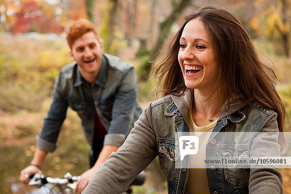 Young couple cycling along riverside in autumn