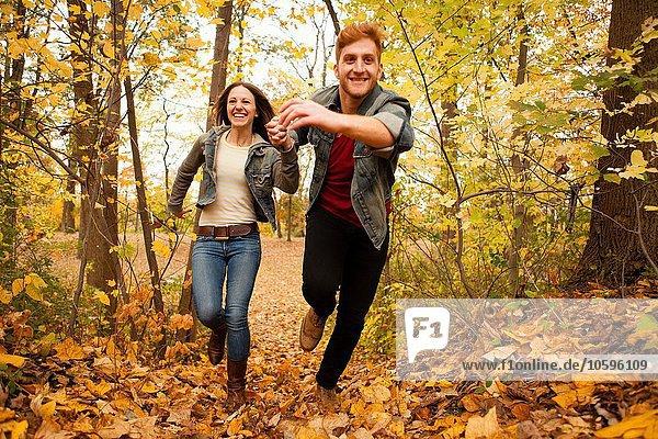 Romantisches junges Paar läuft durch den Herbstwald