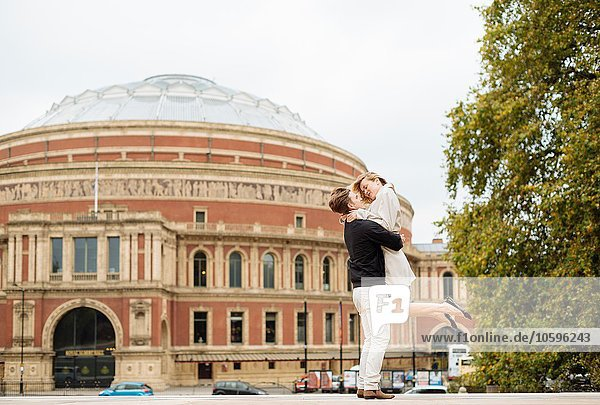 Junger Mann hebt Freundin vor der Albert Hall  London  England  UK