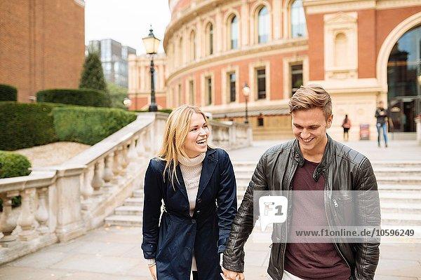 Young couple hand in hand outside Albert Hall  London  England  UK