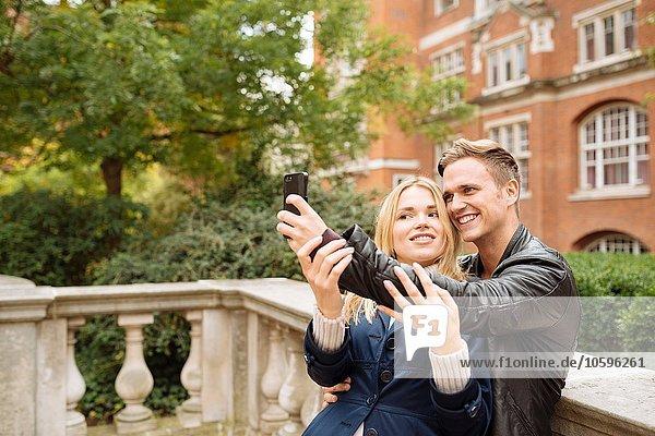 Junges Paar  das sich außerhalb der Albert Hall  London  England  UK  niederlässt. Junges Paar, das sich außerhalb der Albert Hall, London, England, UK, niederlässt.